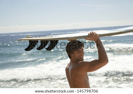 Portrait of handsome young man carrying surfboard by ocean - stock photo