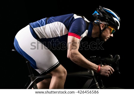 Portrait of handsome young man cycling indoor. Isolated on black.