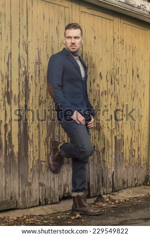 portrait of handsome young man dressed in jeans blazer and military boots posing against old garage doors