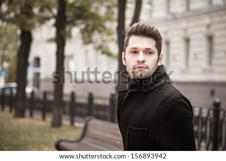 portrait of handsome young man in the autumn park