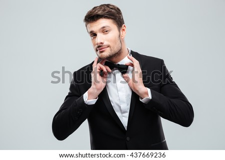 Portrait of handsome young man in tuxedo with bowtie - stock photo