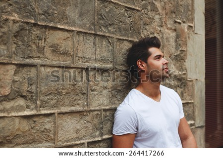 Portrait of handsome young man leaning on brick wall pensive looking up, charming hipster man posing outdoors, fashionable male model dressed causally - stock photo