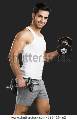 Portrait of handsome young man lifting weights, isolated over a gray background - stock photo