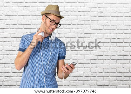 Portrait of handsome young man listening to music  - stock photo