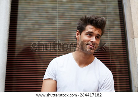 Portrait of handsome young man looking away with smile, charming hipster man posing outdoors - stock photo