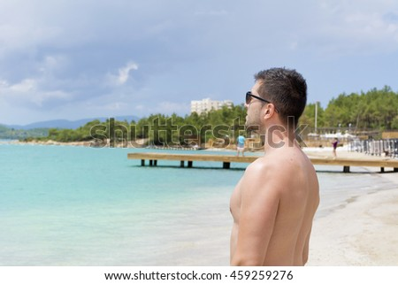 Portrait of handsome young man on a tropical  beach