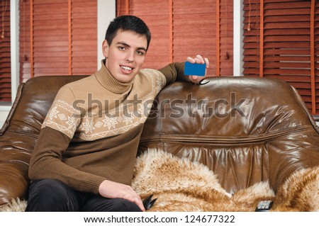 portrait of handsome young man on sofa in the apartment with credit card - stock photo