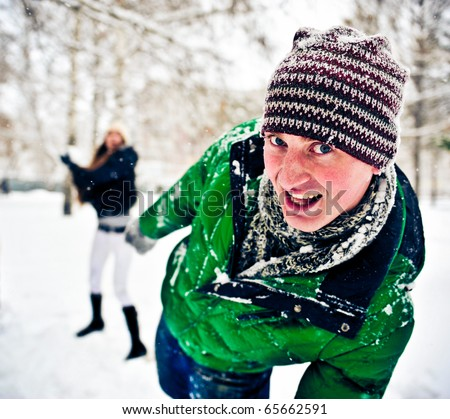 Portrait of handsome young man playing with snow outdoor in winter park on holidays - stock photo
