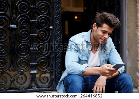 Portrait of handsome young man sending a text message while sitting outside, young student sitting on the stairs typing, cropped shot of a fashionable man using his mobile phone in the city - stock photo
