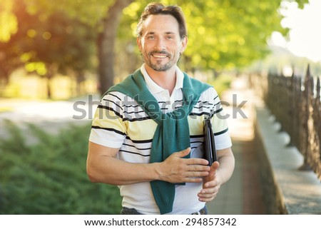 Portrait of handsome young man smiling outdoor. Rich guy in fashionable T-shirt demonstrating healthy life style on nature.