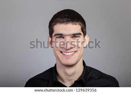 Portrait of handsome young man smiling over gray background - stock photo
