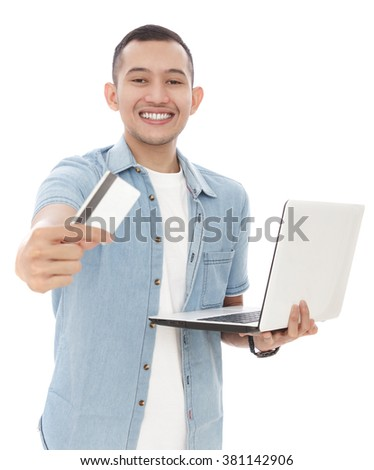 portrait of handsome young man smiling while showing a credit card and holding a laptop isolated on white background - stock photo