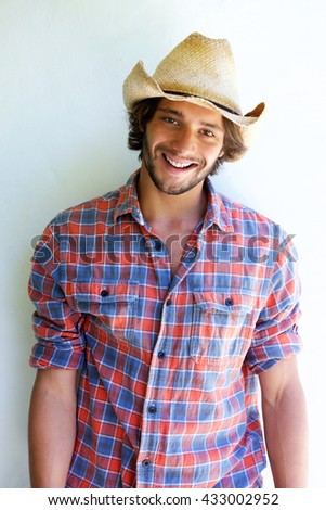Portrait of handsome young man smiling with cowboy hat  - stock photo