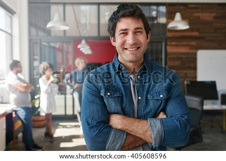 Portrait of handsome young man standing with his arms crossed in creative office. Confident young male creative professional looking at camera and smiling. - stock photo