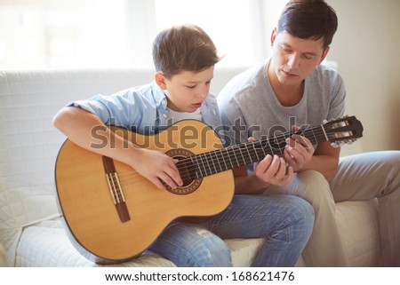 Portrait of handsome young man teaching his son how to play the guitar - stock photo