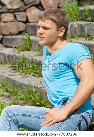 Portrait of handsome young man wearing casual sitting on the stairs in the park - stock photo