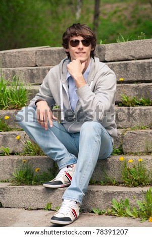 Portrait of handsome young man wearing sunglasses sitting on stairway in park - stock photo