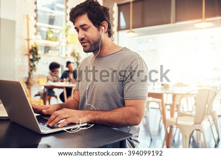 Portrait of handsome young man with earphones working on laptop while sitting at a coffee shop. Young guy at a cafe surfing internet on laptop. - stock photo