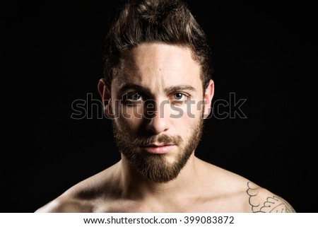 Portrait of handsome young man with tattoos posing. Isolated on black.
