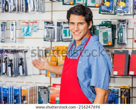 Portrait of handsome young vendor welcoming at hardware shop - stock photo