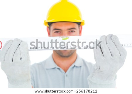Portrait of handyman holding spirit level on white background - stock photo