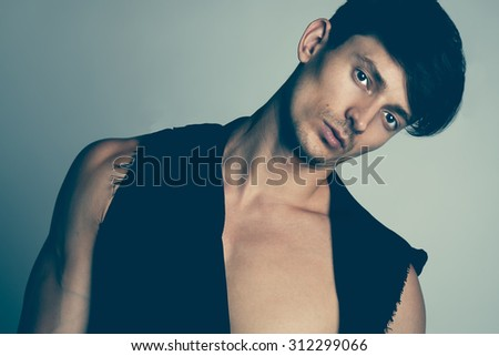 Portrait of hansome male model in black clothes posing over gray background. Close up. Studio shot. - stock photo