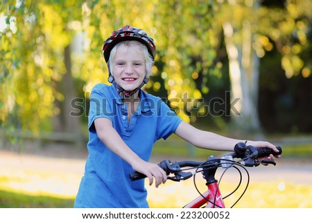 Portrait of happy active teenage boy in safety helmet relaxing after school riding his bike in beautiful park on sunny autumn day