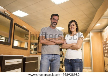 Portrait of happy adult couple with crossed arms looking at camera in bathroom furniture store