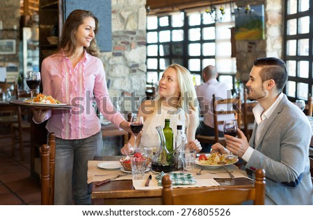 Portrait of happy adults people having dinner and respectful waiter - stock photo