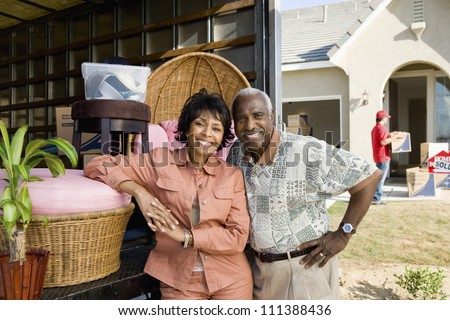 Portrait of happy African American couple moving to their new house - stock photo