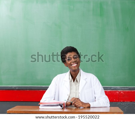 Portrait of happy African American female teacher sitting at desk in classroom - stock photo