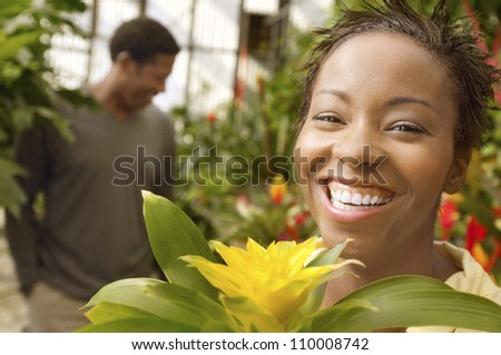 Portrait of happy African American woman with man in background at botanical garden - stock photo