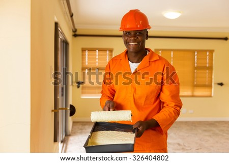 portrait of happy african builder holding paint roller and paint - stock photo
