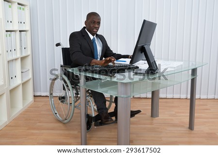 Portrait Of Happy African Businessman Working In Office Sitting On Wheelchair - stock photo