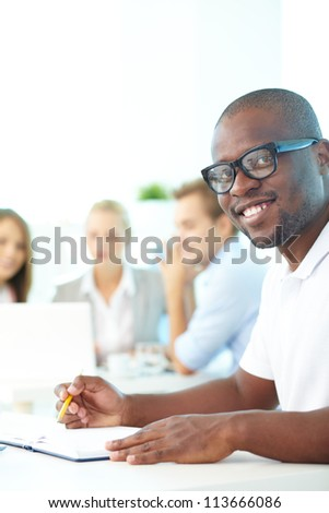 Portrait of happy African guy looking at camera with group of students behind - stock photo