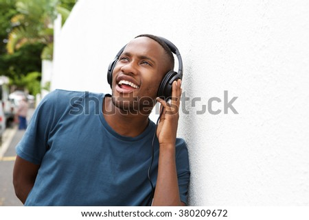 Portrait of happy african man listening to music on headphones outdoors - stock photo