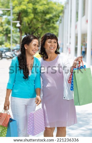 Portrait of happy aged women with paper bags standing outdoors - stock photo