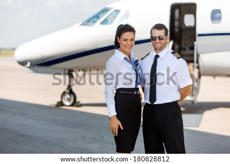 Portrait of happy airhostess and pilot standing against private jet at terminal - stock photo