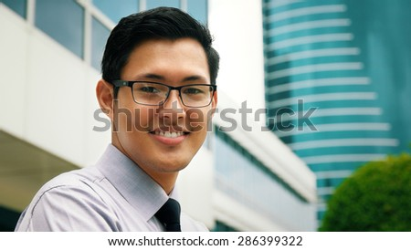 Portrait of happy and confident young asian businessman. The man stands in a street against office buildings and crosses arms looking at camera - stock photo