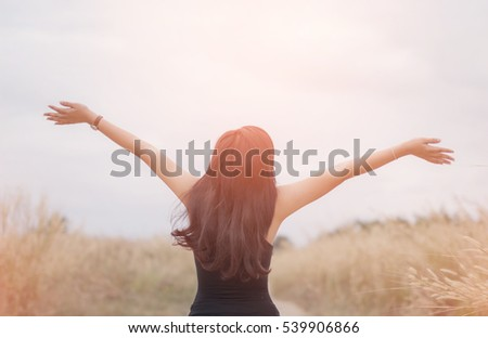 Portrait of happy and enjoying young woman on a meadow on a sunny summer day. Cheerful girl on sunset. Lifestyle and happiness concept.