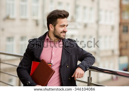 Portrait of happy and handsome bearded businessman holding documents and looking away on the street. - stock photo