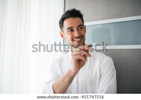 Portrait of happy and smiling handsome businessman showing or poiting something with a pen and looking at one side in the office. Business. - stock photo