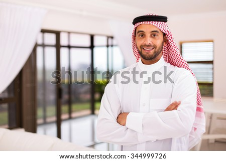 portrait of happy arabian man standing indoors - stock photo