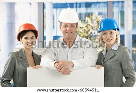 Portrait of happy architects wearing hardhat smiling in office, blank poster for copyspace.?