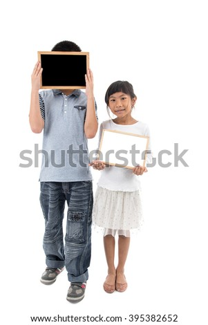 portrait of happy asian boy and girl holding blank blackboard and whiteboard on white, space for your text - stock photo
