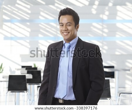 Portrait of happy asian businessman at office lobby, smiling. - stock photo
