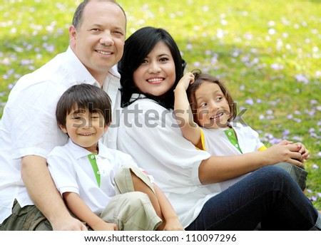 Portrait of happy asian caucasian family in the park - stock photo