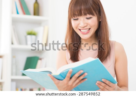 Portrait of happy Asian college girl laughing while reading on book. Young woman at school library.
