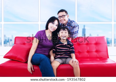 Portrait of happy asian family sitting on couch shot at apartment - stock photo