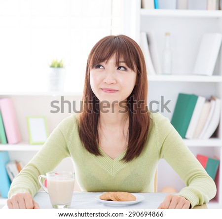 Portrait of happy Asian girl thinking and smiling while having breakfast. Young woman indoors living lifestyle at home.
